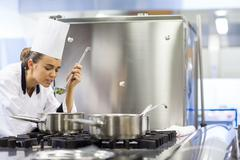Stock Photo of Young pretty chef tasting sauce