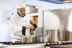 Focused head chef flavoring food with pepper - stock photo