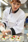 Pretty concentrating head chef preparing dessert - stock photo