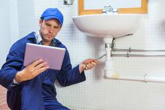 Serious plumber consulting tablet - stock photo