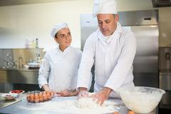 Head chef showing happy trainee how to prepare dough Stock Photos
