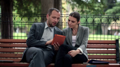 Business people talking and using tablet sitting on bench in park HD Stock Footage