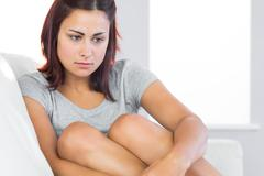 Stock Photo of Thoughtful brunette woman sitting on her couch