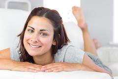 Beautiful young woman lying on her couch in the living room Stock Photos