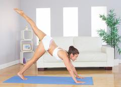 Slim woman stretching her body in yoga pose - stock photo