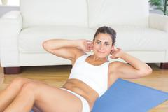 Portrait of fit calm woman doing sit ups on exercise mat - stock photo