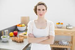 Stock Photo of Peaceful serious woman standing with arms crossed in kitchen