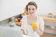 Joyful brunette woman holding a glass of orange juice while sitting in kitchen - stock photo