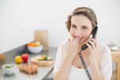 Amused lovely woman sitting in her kitchen phoning with a telephone Stock Photos