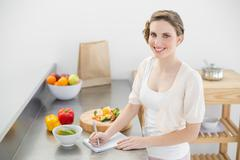 Stock Photo of Lovely woman standing in her kitchen writing a shopping list