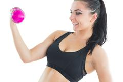 Stock Photo of Natural active woman training with pink dumbbells