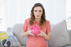 Cute pregnant woman holding a piggy bank while sitting on couch Stock Photos