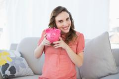 Stock Photo of Smiling pregnant woman shaking pink piggy bank sitting on couch