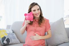 Content pregnant woman shaking pink piggy bank sitting on couch Stock Photos
