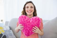 Cheerful pregnant woman holding pink heart pillow sitting on couch - stock photo