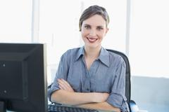 Stock Photo of Cute young businesswoman sitting at her desk with arms crossed