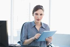 Stock Photo of Lovely businesswoman using her tablet sitting at her desk