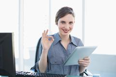 Stock Photo of Attractive calm businesswoman showing thumbs up while holding her tablet