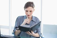 Stock Photo of Thoughtful young businesswoman holding a diary sitting at her desk