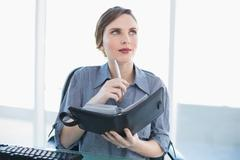 Thinking businesswoman holding her diary while sitting at her desk - stock photo