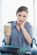 Tired casual businesswoman holding a disposable cup while sitting at her desk - stock photo