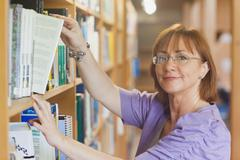 Mature female librarian taking a book off a shelf - stock photo