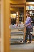 Serious female librarian pushing a cart Stock Photos