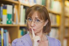 Mature female librarian giving a sign to be quiet standing in library - stock photo