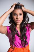 Seductive attractive brunette posing for camera ruffling hair Stock Photos