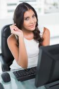 Content cute businesswoman holding pen looking at camera - stock photo