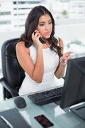 Serious cute businesswoman working at computer phoning Stock Photos