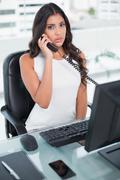 Serious cute businesswoman phoning - stock photo