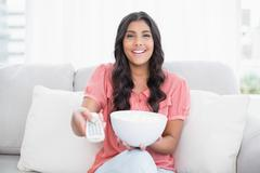 Happy cute brunette sitting on couch holding popcorn bowl Stock Photos
