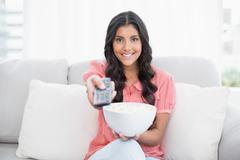 Smiling cute brunette sitting on couch holding popcorn bowl Stock Photos