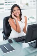 Cheerful cute businesswoman phoning on smartphone - stock photo