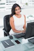 Stock Photo of Content cute businesswoman working at computer