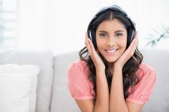 Stock Photo of Happy cute brunette sitting on couch listening to music