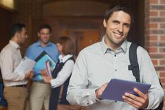 Content male mature student posing in corridor holding his tablet Stock Photos