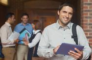 Stock Photo of Content male mature student posing in corridor holding his tablet