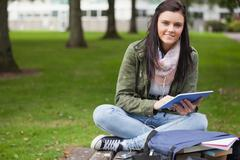 Happy brunette student using tablet sitting on bench - stock photo