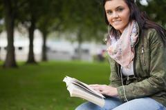 Gleeful brunette student sitting on bench reading - stock photo