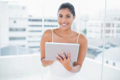 Cheerful toned brunette holding tablet Stock Photos