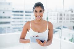 Gleeful toned brunette using tablet - stock photo