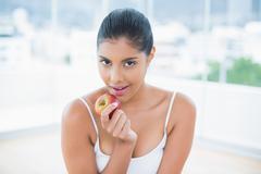 Happy toned brunette holding apple Stock Photos