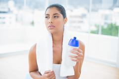 Serious toned brunette with towel holding sports bottle Stock Photos