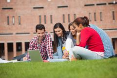 Stock Photo of Five casual students sitting on the grass looking at laptop