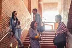 Casual students standing on stairs chatting - stock photo