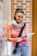 Pretty smiling student taking notes next to notice board - stock photo