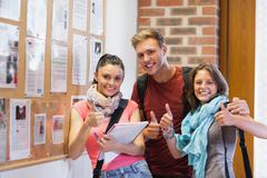 Three smiling students standing next to notice board showing thumbs up - stock photo