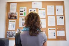 Student studying notice board - stock photo
